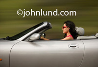 Woman driving sliver convertible with the top down, and wearing pink sunglasses while speeding down the road. Woman in convertible pic.