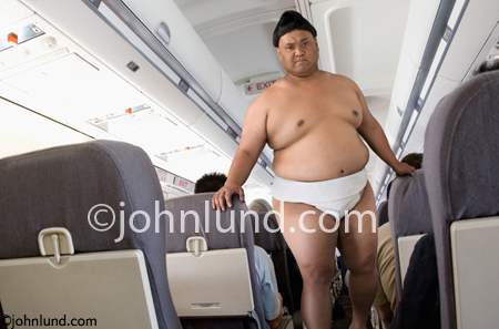 Funny picture of a Japanese Sumo Wrestler in an airliner. The wrestler is wearing his wrestling outfit. Sumo Wrestler pics.