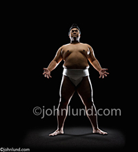 Stock photo of an imposing looking Sumo wrestler. This huge massive man is being backlit making him look even scarier. Sumo wrestler pics.