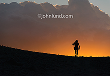 A photographer, tripod and camera slung over his shoulder, walks over a ridge against a brilliant sunset in an image about exploration, creativity and following your passion.