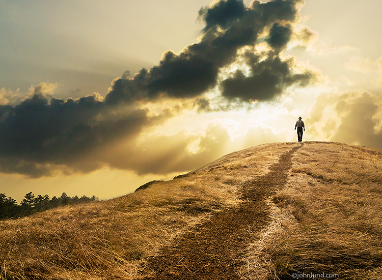 A lone figure nears the crest of a hill silhouetted against a late afternoon sun as he walks a path in solitude and contemplation in this concept stock photo.