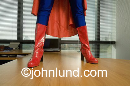 Stock photo of a woman superhero's boots and legs standing on a desk in an office.  Picture of superhero from knees down. Superhero standing on a wooden table.