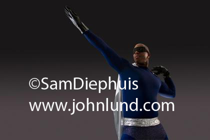 Picture of a black superhero in a blue costume with a silver cape. Black gloves on his hands. African American super hero pic.