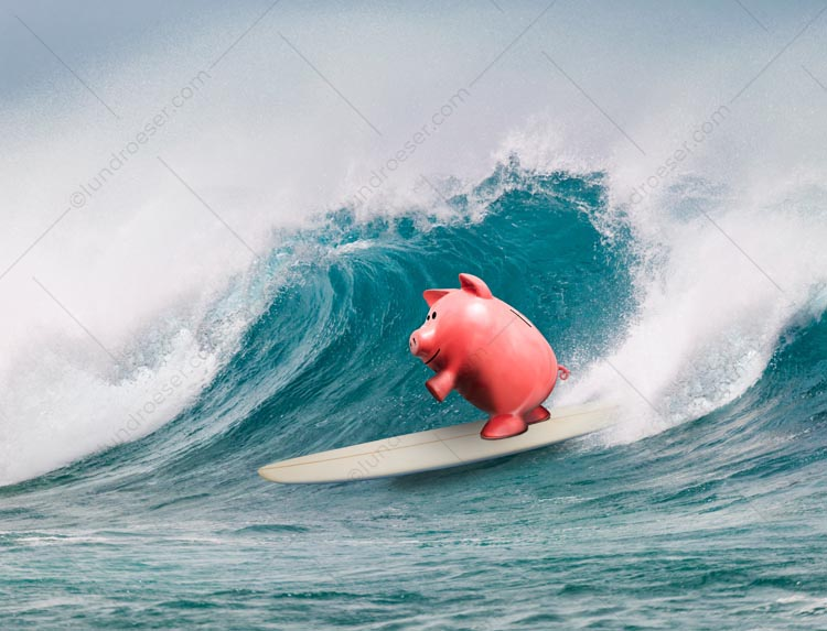 A piggy bank surfs a huge wave in a stock photo about financial success and the freedom it offers.