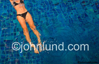Stock photo of a woman's body gliding underwater in a pool with a tile bottom shot in Koh Samui, Thailand.  LIfestyle, leisure, and luxury spa resort pics.