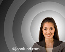 A smiling woman has grey concentric rings eminating from her face in a stock photo about demographics, target audiences, and accessing individuals.