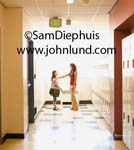 Photo of a teacher talking to or greeting a young student in the school hallway in front of the wall lockers that line the corridor.