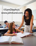 Picture of a middle school teacher assisting a young girl student in the classroom.  The African American teacher is smiling and helping a young white girl with her schoolwork. The blonde girl is a pre-teen and has a yellow pencil in her hand.
