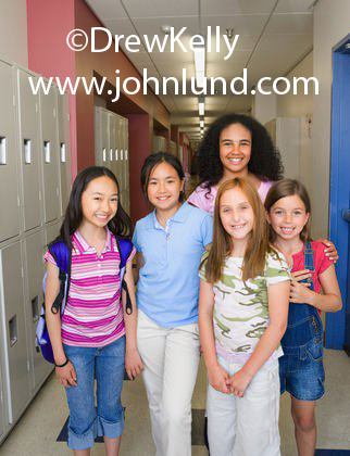 Photo of a group of school kids in grade school. The kids are standing in the hallway and their teacher is standing behind them. Group of young elementary school girls with their teacher in the school hallway. Ad pics with kids.