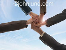 Photo depicting business Teamwork shown in a spiral hand clasp with an upward view and the sky in the background.