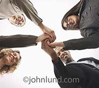 Four people in business attire join hands in teamwork and co-operation in this photo about joining together for success.