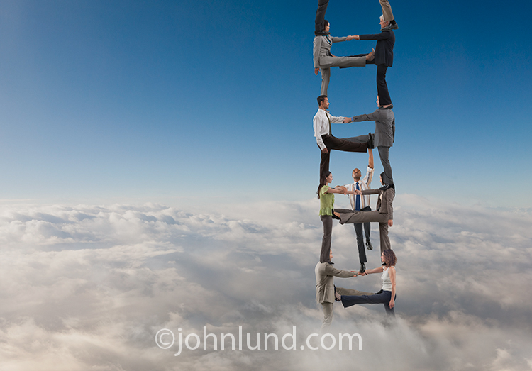 This teamwork success image shows a man climbing a ladder made from people on each other's shoulders rising high above the clouds.