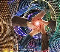 The hands of five individual come together in technology teamwork hand clasp while engulfed in light trails creating energy patterns showing communications technology.