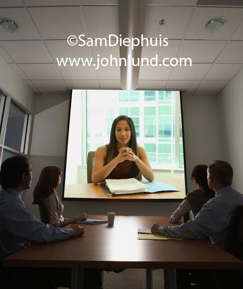 Pictures of teleconferncing. Video conference session with a large screen with a Chinese woman executive in a business meeting. Pics of teleconference using large video screen for advertising.
