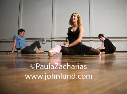 Three Dancers Stretching And Warming Up Before Dance Routine