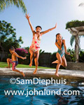 Grandmother and grand children jumping in a swimming pool. Faimly fun during vacation travel. Kids having fun in the pool with grandma with a tropical resort looking background. Beautiful clear blue sky.