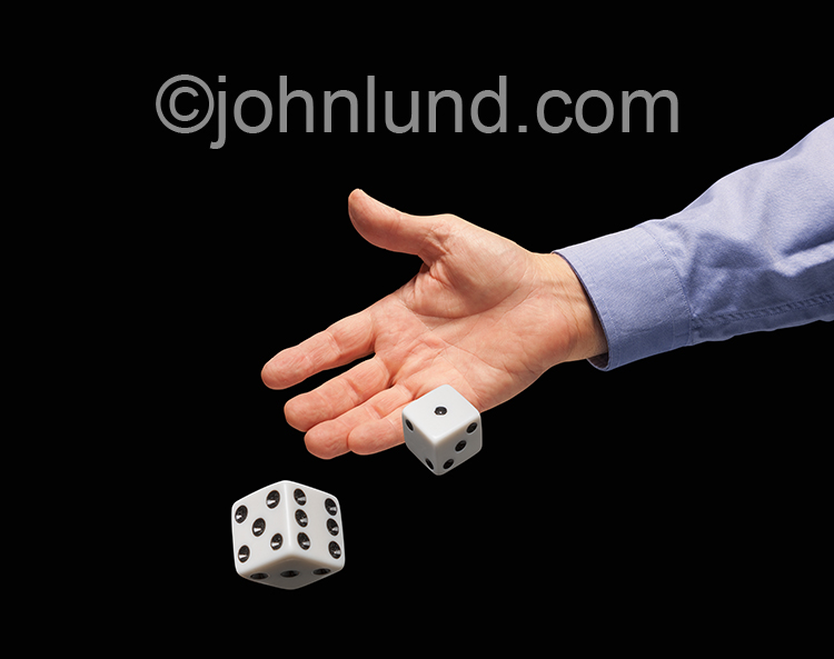 A hand throws dice on a black background in a stock photo about gambling and risk.