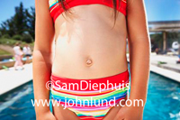 A pre-teen, or elementary aged young child is wearing a two piece swimming suit, a bikini, with stripes. The photo is of her torso only, focused on her belly button.