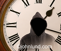 Time theft, and a time thief, are portrayed in this stock photo showing a hooded figure sans face against the backdrop of a clock.