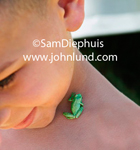 Summertime picture of a young boy with a tiny little green frog crawling around on his neck. He is happy about the whole thing. Boy is of mixed race heritage.