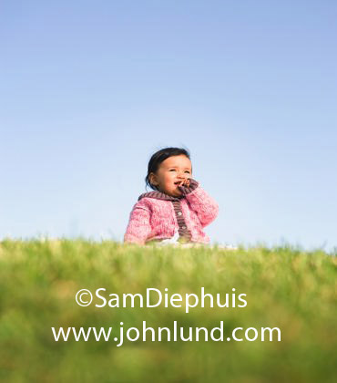 Toddler sitting on a grassy hill with a blue sky background. The cute ...