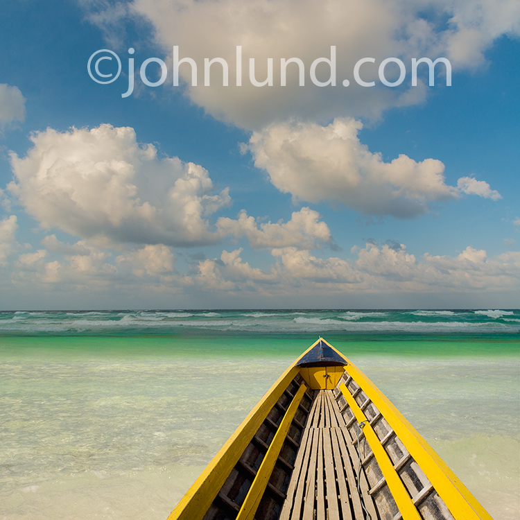 A boat floats in clear tropical waters in a stock photo about tropical vacations, relaxation, solitude and getting away from it all.