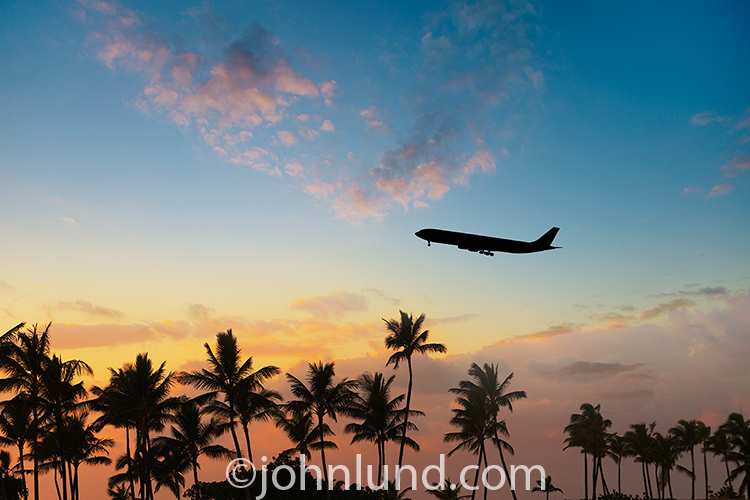 A jet aircraft and palm trees are silhouetted against a tropical sunrise in an image about vacations, travel and getting away from it all.