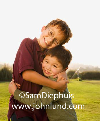 Two young Asian brothers hugging each other in the park outdoors. The older brother is wearing a maroon shirt and glasses and the younger brother is wearing a green shirt.  They are standing in a large grassy area. Kids pics for ads.