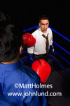 Stock photo of businessmen fighting. Two businessmen are facing off in a boxing ring.  One man has a blue dress shirt and large red boxing gloves. Funny people doing funny things for business advertising photography.