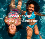Picture of two little Asian girls playing in a swimming pool. Happy smiling girls laying on their backs partially submerged giggling and laughing and having fun in the swimming pool. Ethnic children in a swimming pool.