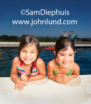Two adorable cute little girls are in the swimming pool with their arms on the cement at the side of the pool. They have wet hair and are smiling happily at the camera. Pics of fun at the pool in the summertime of young kids playing.