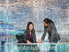 Women working in technology is illustrated in this stock photo of two women discussing technology in an environment of complex computer circuitry.