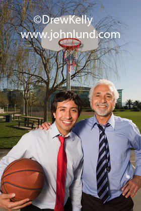 Stock photo of a couple of hispanic businessmen playing basketball together. One is a senior executive with gray hair and a gray goatee, and the other is a young executive just beginning his career. Executives playing basketball pics.