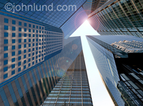 Low angle view of an urban landscape of high rise office buildings in which the sky above takes on the shape of an upwards pointing arrow in a metaphor for growth and success.