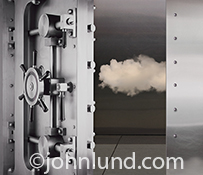 A cloud is seen inside a bank vault behind a half-open steel safe door in an image about security and cloud computing in the age of Internet hackers.