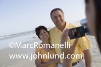 Senior hispanic couple having thier video taken as they stroll on the beach.  He is wearing a yellow shirt and she has on a yellow print dress. They both have short hair and are smiling. Arms around each other. Senior Hispanic Pics.