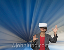 A woman wears virtual reality headgear standing in a tunnel of blue streaks in a stock photo about VR, technology and the future.