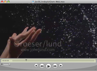 Water is tossed up, sparkling against a black background, by a pair of hands, in a super slow motion stock video