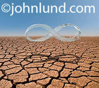 This water scarcity image features a mobius strip, created from a water splash, hovering over a large expanse of dry cracked earth.