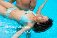 An woman of hispanic descent is floating on her back while a man has his arms under her keeping her afloat.  She is relaxing and enjoying the therapy treatments. Luxury spa and resort photo.