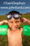 A very young child, a boy, is wearing water wings and swimming goggles and has a big smile on his face as he takes up a body builder pose showing off his water wing muscles.