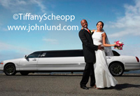 A middle aged African American couple, just married, pose hugging each other in front of a white stretch limo are one happy pair. Bride is wearing a white wedding dress and the groom is in a tuxedo.