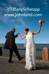 A happy laughing newlywed couple are dancing with each other on a pier with the ocean in the background.