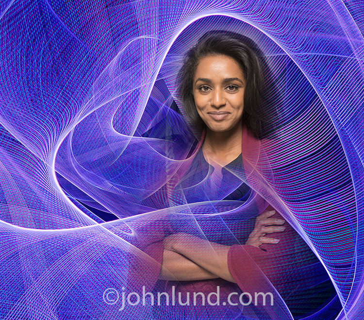A woman, well connected with technology, is illustrated in this stock photo of a smiling and confident African American businesswoman surrounded by complex patter of light trails indicating big data, streaming information, and communications technology.