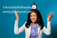 Stock image of a young asian woman balancing a clock on the top of her head. She has her hands up in the hair and a hopless expression on her face. The attracitve young woman has on a white jacket and a lavender blouse.