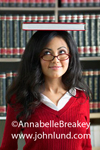 Picture of a young hispanic or asian woman with a book balanced on the top of her head. Behind her are bookshelves lined with books.  The beautiful young woman has long black hair and is wearing a purple sweater and eyeglasses.