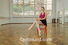 A ballerina is seated on a red chair in a dance studio in this stock photo about confidence, preparation and tranquility.