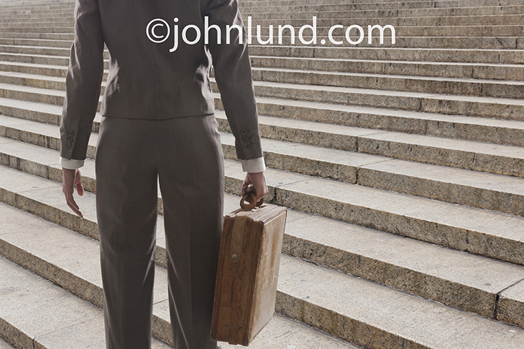 A businesswoman, holding a briefcase, stands in front of seemingly endless stairs facing challenge and opportunity.