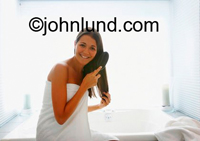 Beautiful woman sitting on the edge of the bath tub wearing a white bath towel and brushing her long brown hair.  She has a lovely smile and is back lit through a window behind her.