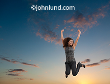 A successful woman celebrates her achievement by jumping up estactically into the dusk sky arms upraised in victory, and wearing a wide smile of happiness.